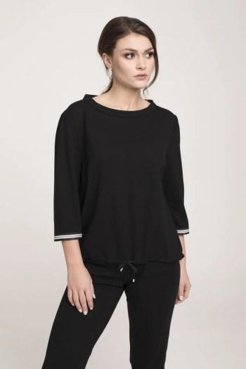 Modelka w czarnym dresie z lampasami Vito Vergelis. Czarna bluza ze stójką i taśmami i czarne spodnie Vito Vergelis.