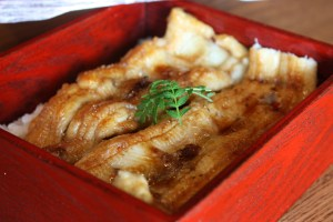 a bowl of rice topped with cooked conger eel of Awaji Island