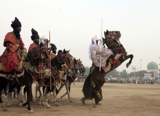 Men dressed in traditional clothes ride horses during Durbar festival in Kano