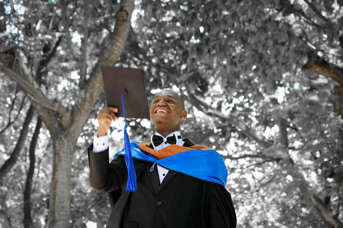 A college grad in his graduation gown and cap in hand