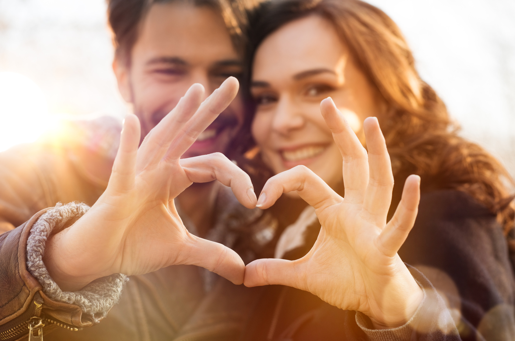 Closeup of couple making heart shape with hands