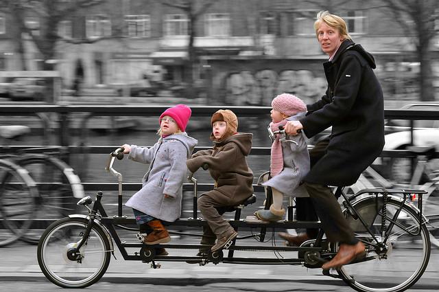 Pessoa com três crianças na bicicleta
