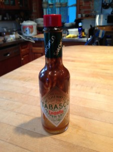 An empty bottle of Tabasco I keep shoving aside when I look in the cabinet for something else. TRASH.