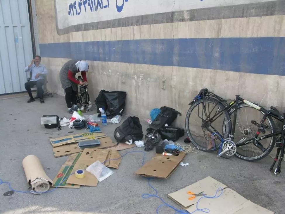 Making cartons on the footpath in Tehran with cardboard found on the street.