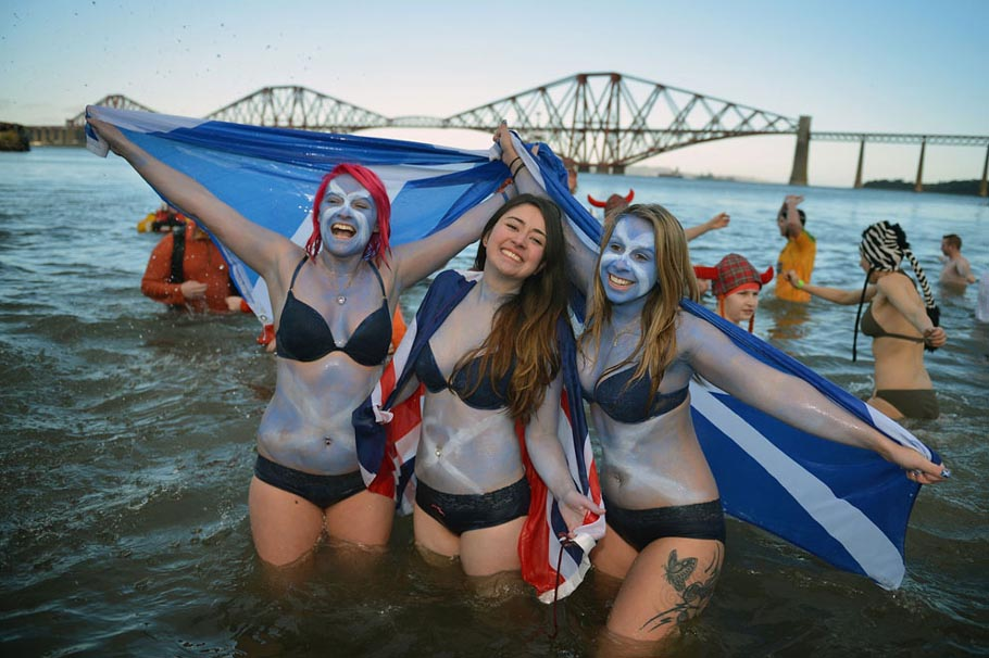 Girls holding saltire flags join around a thousand New Year swimmers, many in costume, who braved freezing conditions in the River Forth in front of the Forth Rail Bridge during the annual Loony Dook Swim in South Queensferry, Scotland, on January 1, 2013. Thousands of people gathered last night to see in the New Year at Hogmanay celebrations in towns and cities across Scotland..