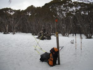 The summit cairn with packs and skis