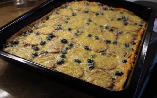 Hausgemachte Pizza mit Salami, Pilzen und Oliven