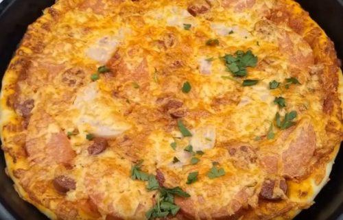 Pizza mit Wurst und Schinken im Ofen