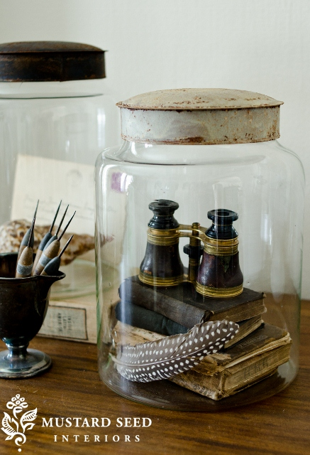 Jarred collection of old books, feathers and binoculars - via Mustard Seed Interiors