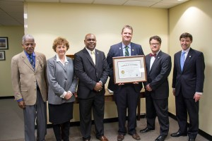VLEPSC Chairman and Brunswick County Sheriff Brian Roberts presents ABC's certificate of initial accreditation to, from left, Commissioner Henry Marsh, Commissioner Judy Napier, Special Policy Advisor for Law Enforcement Ryant Washington, Chairman Jeffrey Painter and Chief Operating Officer Travis Hill.