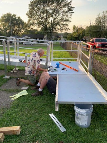 Volunteers Help Dismantle A Wheel Chair Ramp