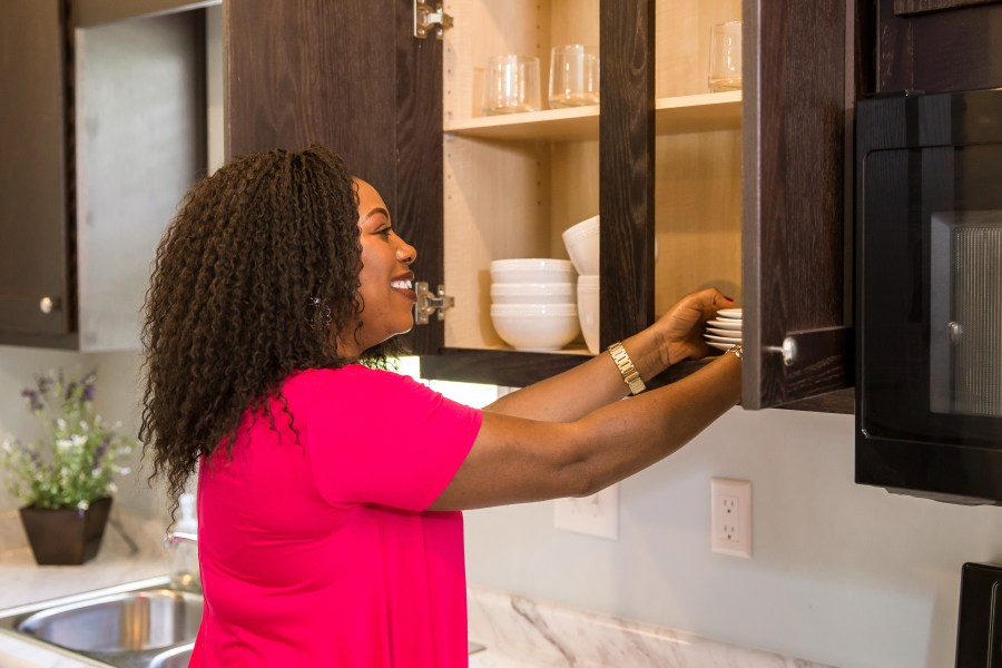 Woman organizing dishes in the kitchen cabinet.