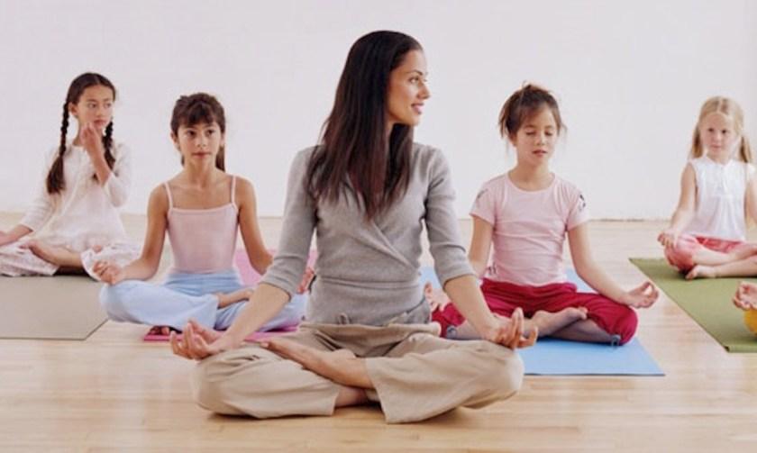Woman teaching children (7-10) yoga
