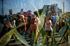 As seen reflected in a window, participants walk along Atlantic Avenue in the Faith, Freedom, Justice March held in Virginia Beach, Va., on Saturday, February 25, 2017.