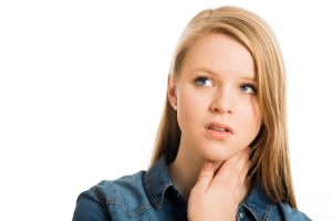 Image of a teenage girl holding her throat and looking worried