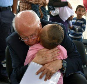 Secretario de Salud, José Narro, abraza a niña, en Querétaro. Foto de Secretaría de Salud