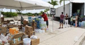 Voluntarios guardan la comida y los artículos que la gente llevó al centro de acopio de Ponce. (Voces del Sur)