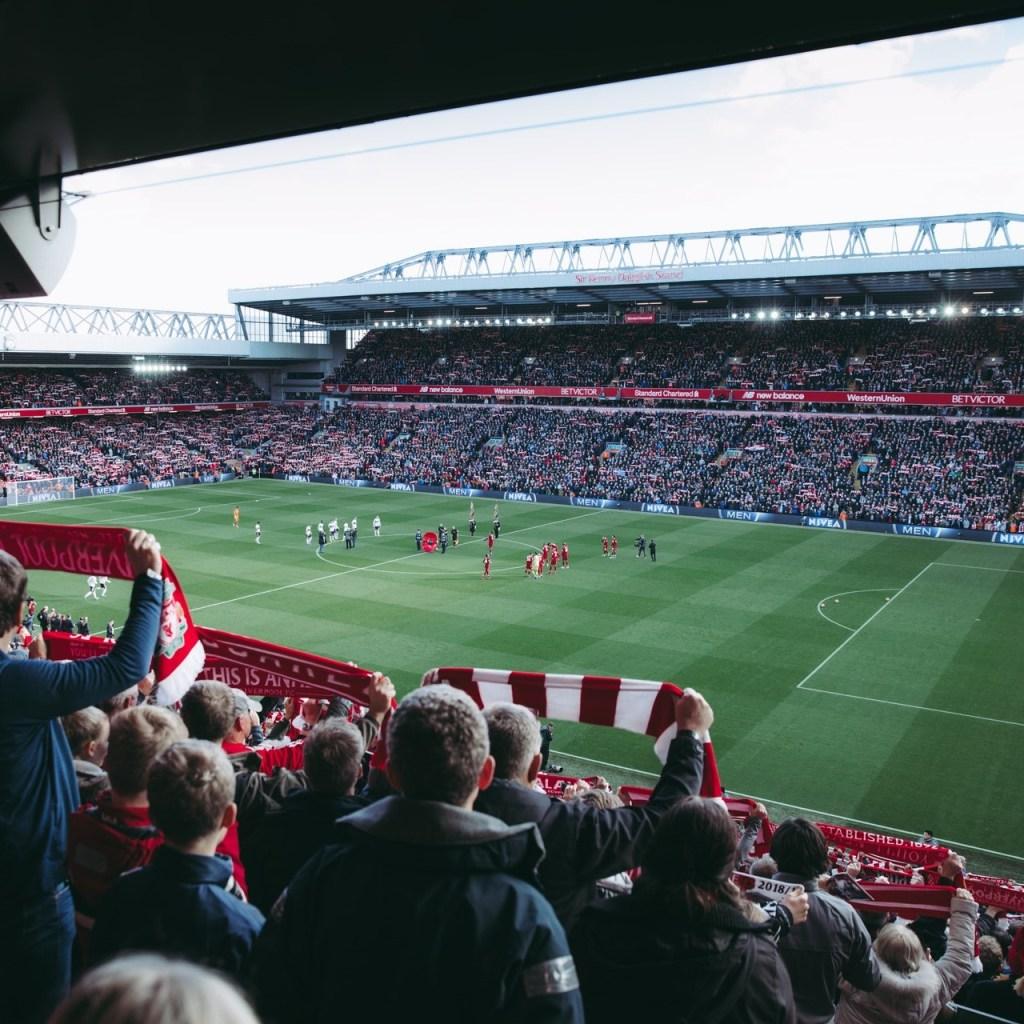 Voetbalfans in het Anfield stadion van Liverpool FC. De voetbalclub komt uit de voetbalstad Liverpool.Door Hier op te klikken kom je in het overzicht van alle voetbalsteden uit het Verenigd Koninkrijk.