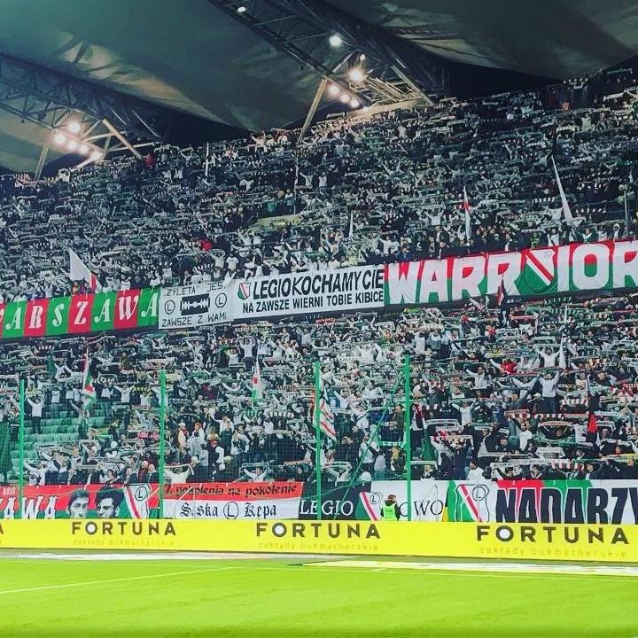 De Legia Warschau fans tijdens een competitiewedstrijd in actie. De Legia supporters staan wekelijks massaal achter hun club. Door te klikken op de afbeelding kom je terecht op de pagina van voetbalstad Warschau.