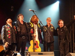 Five musicians arm in arm at the end of a 2016 concert. Tom Wilson is in the middle with a yellow guitar.