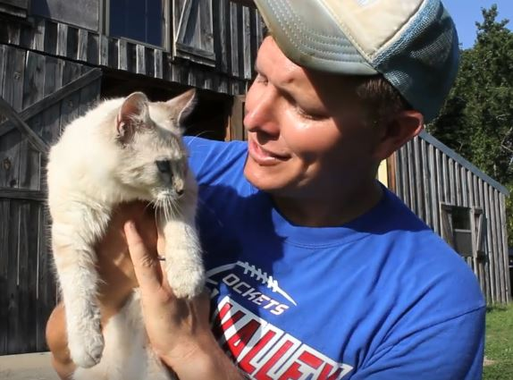 Destin Sandlin holding and looking at a white cat as they get ready to learn