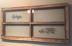 "wood-framed, four-pane window with ""Life begins"" in script in the upper left pane and ""with coffee!"" in the lower right pane. Coffee is in capital letters."