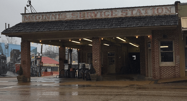 Old time gas station with two pumps under a brick roof. Old lettering says McGinnis Service Station
