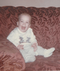 Kevin laughing while sitting on a couch. He's about a year old.