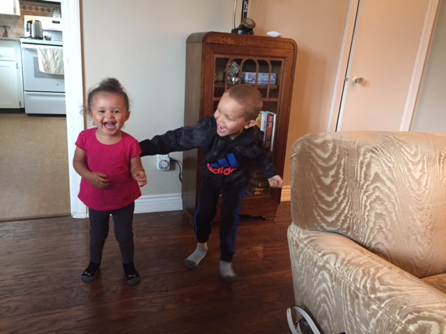 VIenna laughs looking into the camera while Ryker looks at her, also laughing. She's wearing a bright pink dress with grey tights and has her hair in a bun. Ryker is wearing jeans and a hoodie. His hair is closely cropped.