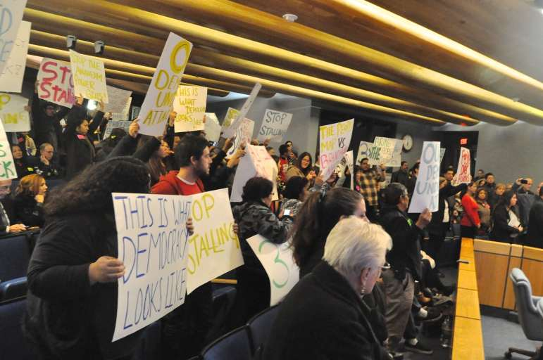 Protesters crowd the speaker's podium at Tuesday night's Anaheim City Council meeting.