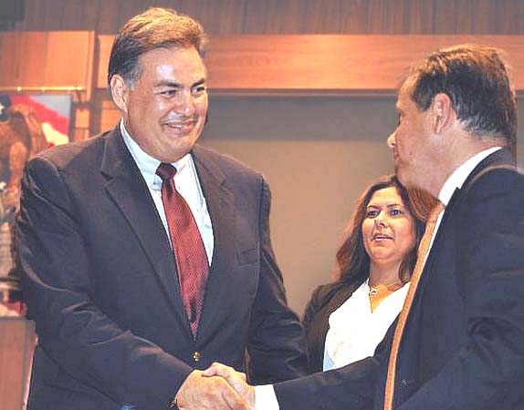 Santa Ana City Manager David Cavazos shakes hands with Mayor Miguel Pulido while Councilwoman Michele Martinez looks on. (Photo by: Adam Elmahrek)