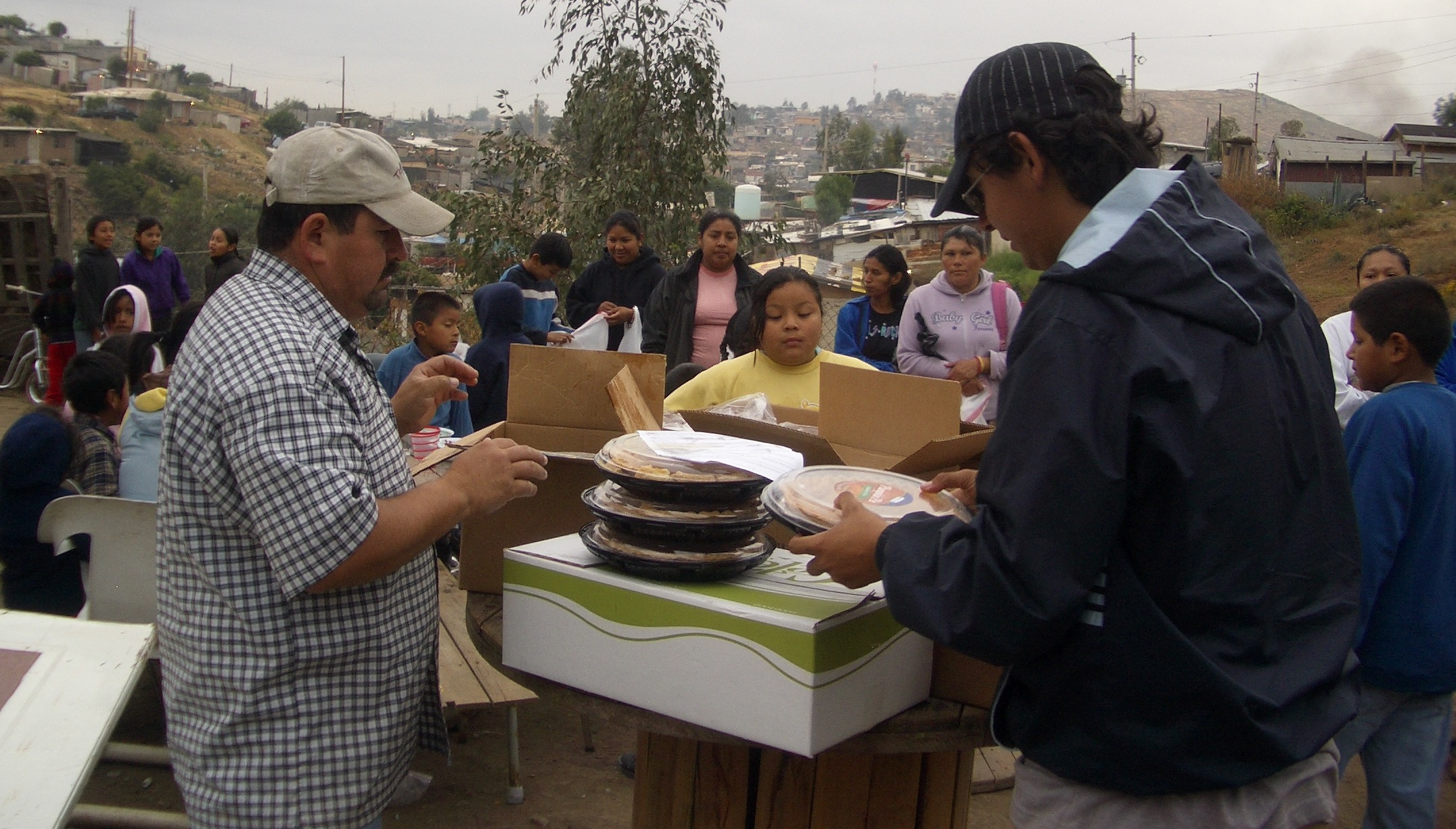 Vicente (left) distributing food to families.