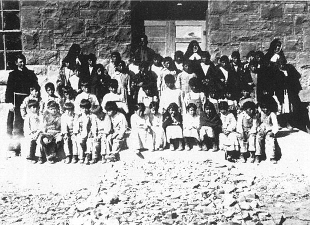 1923. Fr. Anthony Kroger (left) and the first enrollment of students.