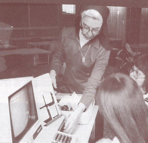 Sr. Alice Patrick taught business courses in the High School. Here she is supervising the work of two students.