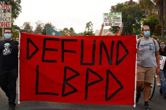 "Two people at the front of a march hold a banner with ""Defund L B P D"" written across it."