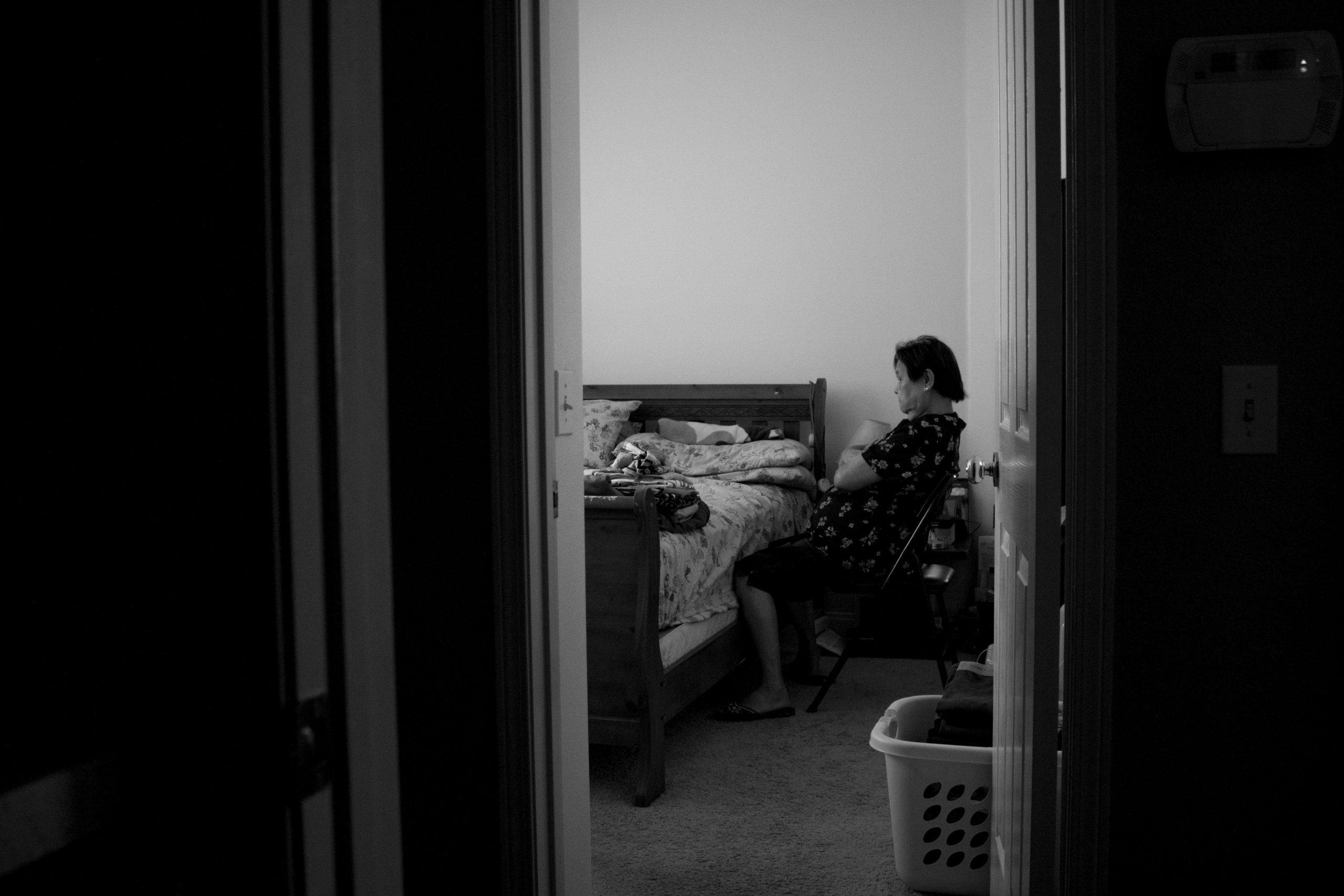 Through an open door, a woman is seen sitting back in a small chair with her arms folded, staring at an empty bed.