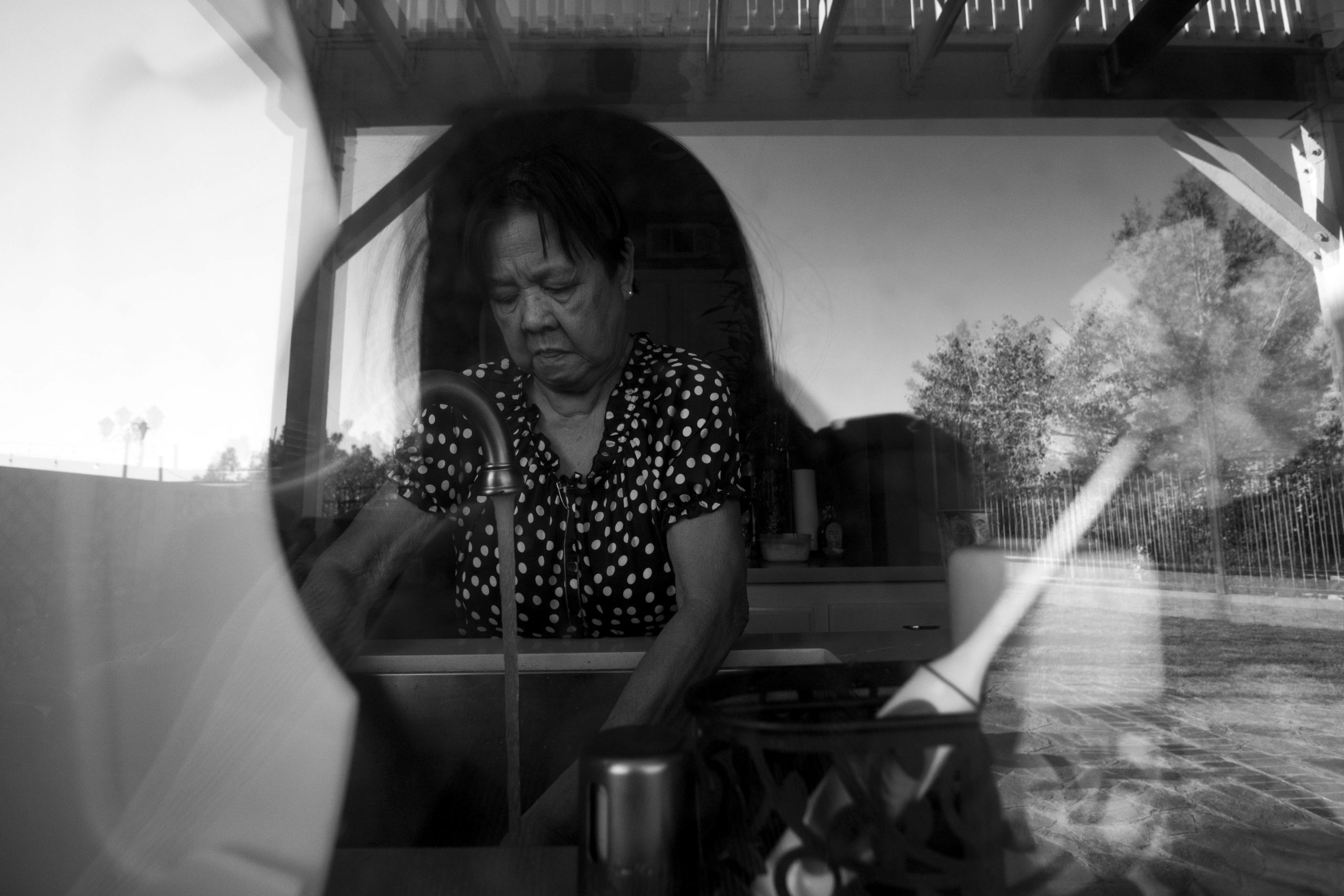 Through a window, a woman is seen washing dishes.