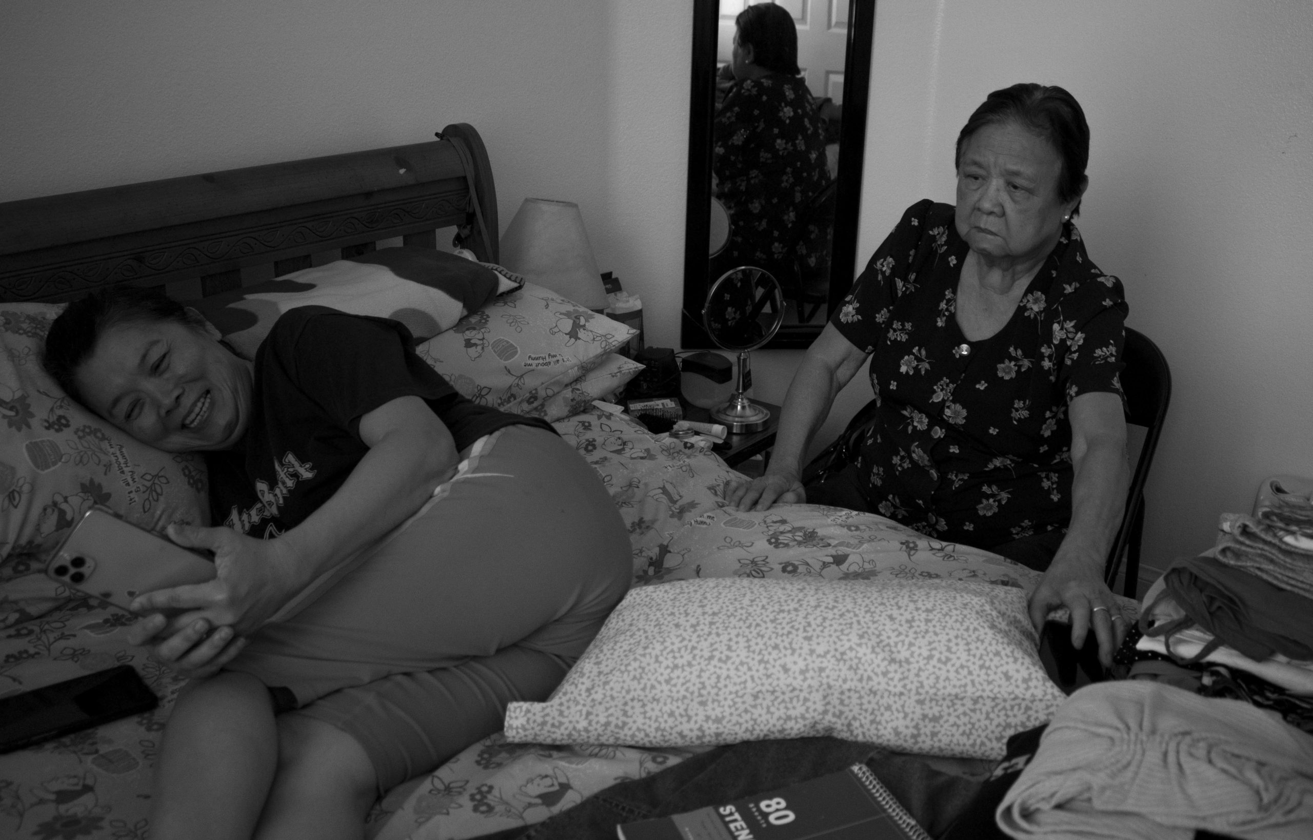 An older woman sits in a chair next to bed while a woman on the bed cries while looking at a phone.