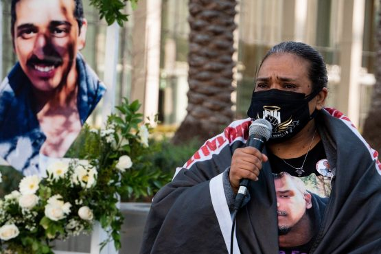 Rosa Moreno stands to the right with a microphone held up to her masked face. To her left is a cut-out picture of her son, Cesar Rodriguez.