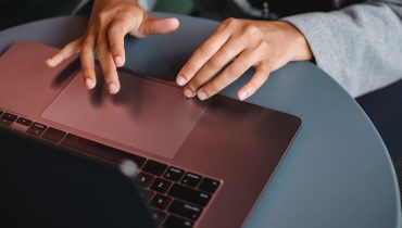 A woman's hands are touching the touchpad of a laptop.