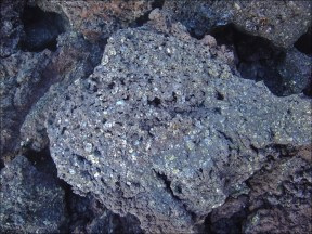 Picrite basalt, or picrobasalt, is dark with yellow-green olivine phenocrysts (20 - 50%) and black pyroxene, mostly augite. The olivine-rich picrites that occur with other more common basalts of Hawaiian volcanoes are the result of accumulation of olivine crystals either in a portion of the magma chamber or in a caldera lava lake. Picrite basalts are commonly erupted at oceanic island volcanoes such as Mauna Kea and Mauna Loa in Hawaiʻi, Curaçao and the Piton de la Fournaise on Réunion Island. Image: Picrite basalt (formerly called oceanite) found in the Grand Brûlé (SE slopes of the Piton de la Fournaise) on Réunion Island. (© David Monniaux, via Wikipedia)