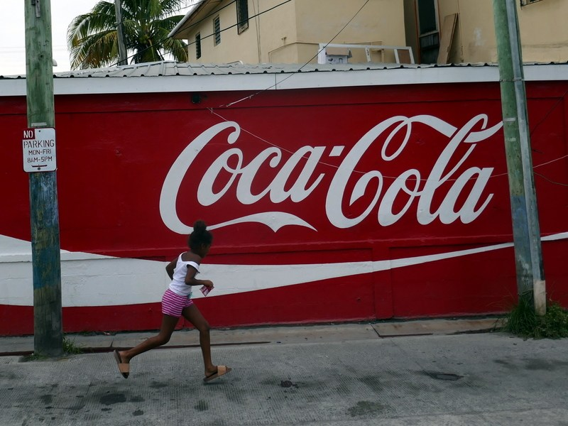 A girl running in front of a Coca Cola sign in Belize City.