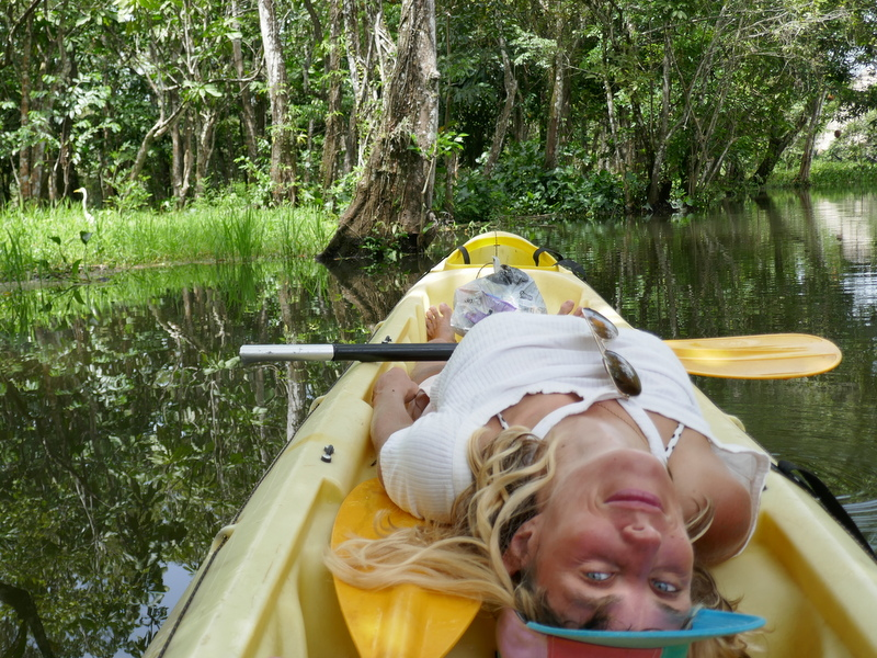 Anete in a kayak on one of the side rivers of the Rio Dulce, with a bird in the background.