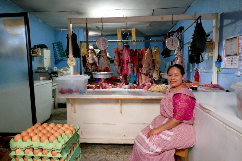 Lady proudly sitting in meat shop in the market of Cobán, Guatemala.