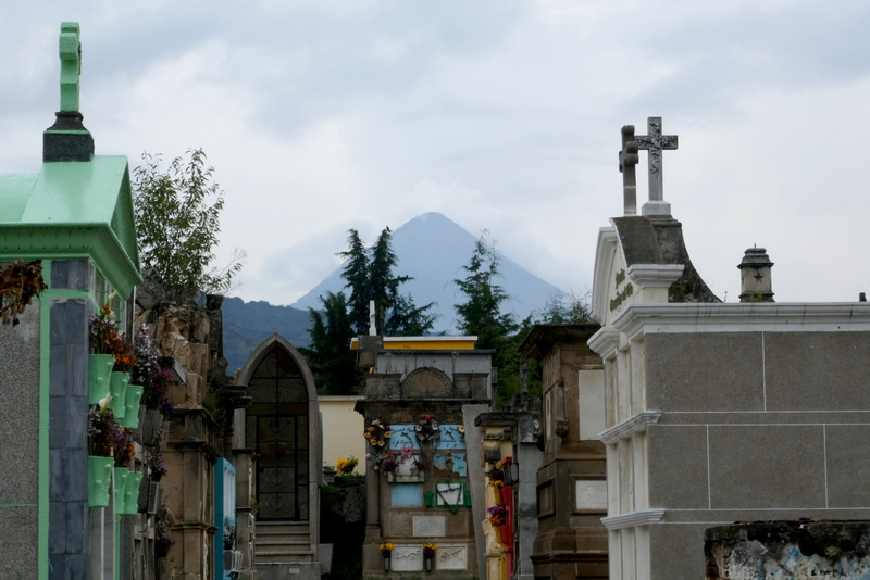 Colorful graves in Xela graveyard, volcano in the background.