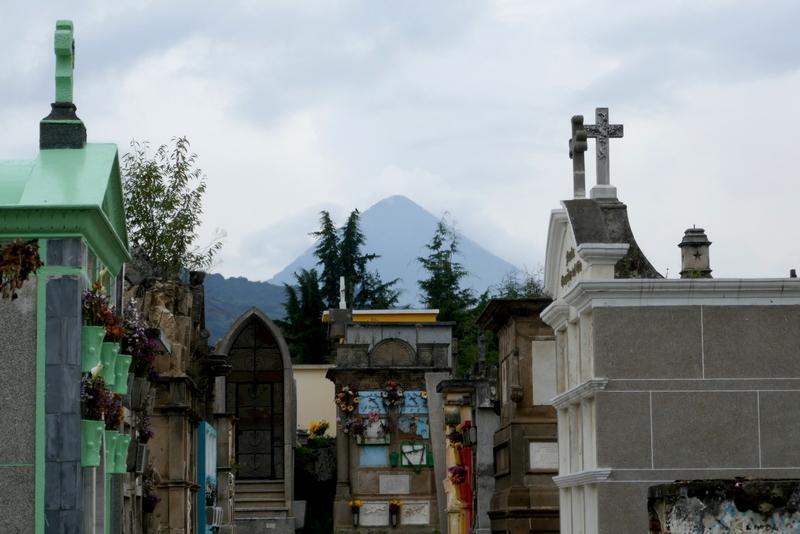 Colorful graves in Xela graveyard, volcano in the background.