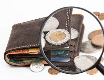 Geldbörse mit Münzen unter einer Lupe