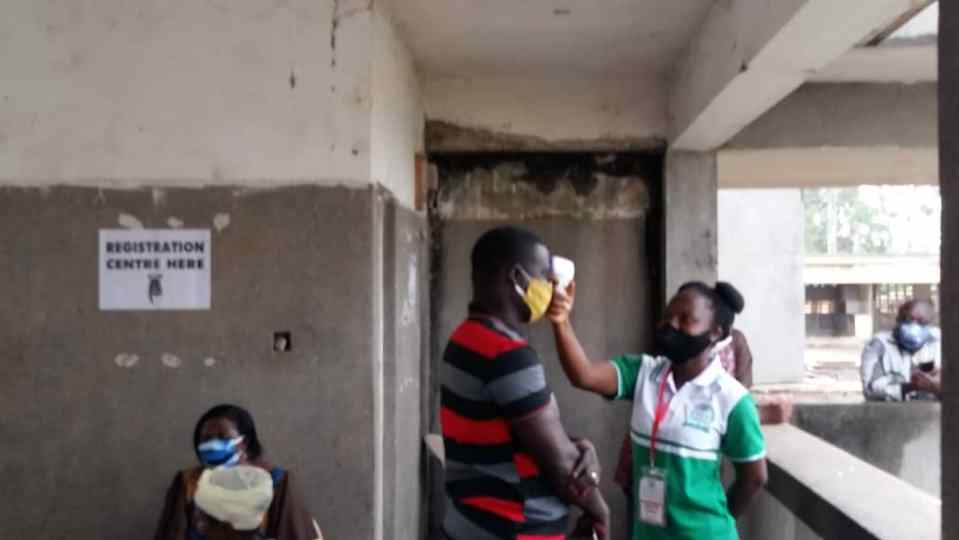 A health official checking temperature of an applicant at the Ho SSNIT flats Registration Centre