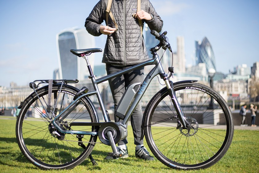 A cyclist posing with his VOLT Infinity e-bike against the London skyline