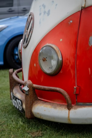 Red and white Volkswagen split screen camper with bottle opener on front bumper